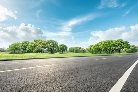 Foto de Country road and green forest natural landscape under the blue sky - Imagen libre de derechos