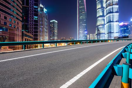 Photo pour Shanghai modern commercial office buildings and empty asphalt highway at night - image libre de droit