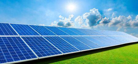 Photo pour Photovoltaic solar panels and green grass on sky background,green clean alternative energy concept. - image libre de droit