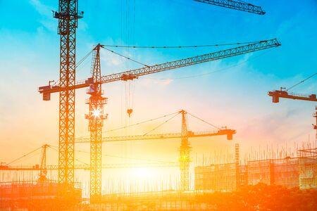 Photo pour Tower crane and building construction site silhouette at sunrise. - image libre de droit