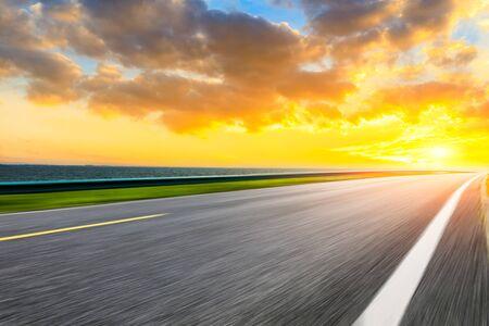 Photo for Motion blurred asphalt highway and lake natural landscape at sunset. - Royalty Free Image