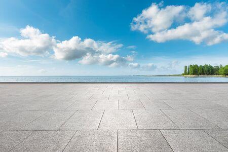 Foto de Empty square floor and lake with tree under blue sky. - Imagen libre de derechos