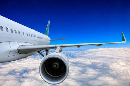 Photo pour Commercial airplane flying above blue sky and white clouds. - image libre de droit