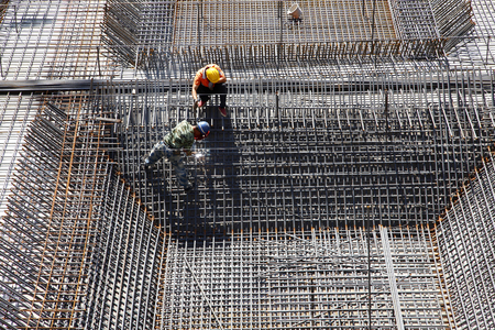 worker in the construction site making reinforcement metal framework for concrete pouring