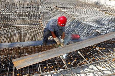 The welding worker in the construction site making reinforcement metal framework for concrete pouring