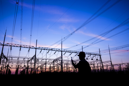 Photo for Power workers at work, silhouettes of power towers - Royalty Free Image