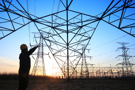 Photo pour In the evening, electricity workers and pylon silhouette - image libre de droit
