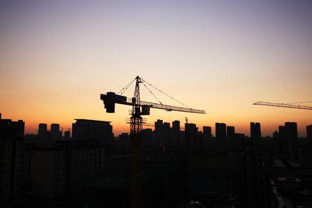 Photo pour Tower cranes build residential buildings at nigh - image libre de droit