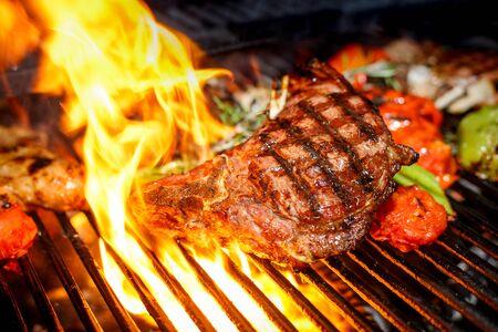 Photo pour steak cooking on fire with vegetables - image libre de droit