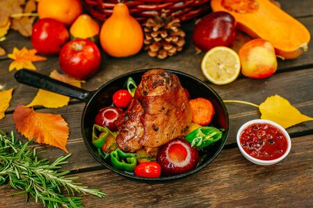 Photo pour Autumn table setting with pumpkins. Thanksgiving dinner.baked pork shank with vegetables - image libre de droit