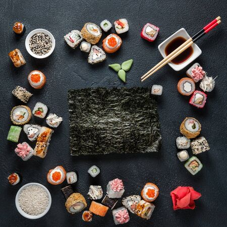 Photo for A set of traditional Japanese dishes on a dark background. Sushi rolls, nigiri, rice, pickled ginger. Frame made of Asian cuisine. - Royalty Free Image