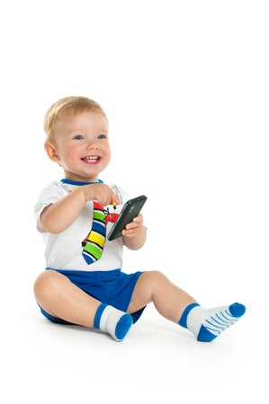 happy boy sits and plays with a mobile phone