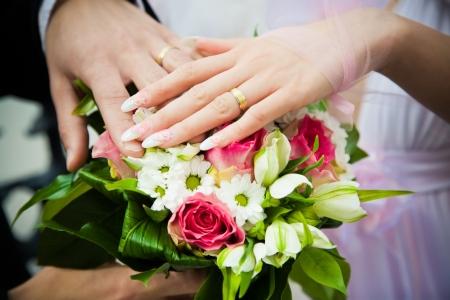 Foto de hands of newly married with wedding bouquet - Imagen libre de derechos