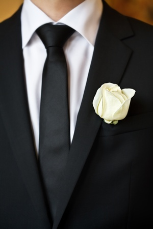 white rose on the suit of groom