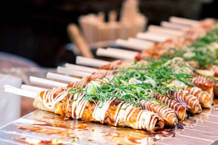Foto de Okonomiyaki on wooden sticks with soy sauce and mayonaise topped with green onion at Nishiki market, Kyoto, Japan - Imagen libre de derechos