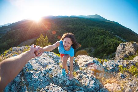 A woman is climbing a stone. Helping hand. A friend helps a girl to climb a mountain. Teamwork. Climbing at sunset.