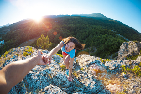 A smiling woman is climbing a stone. Friendly hand of help. A partner helps a girl to climb a mountain. Teamwork. Climbing at sunset.