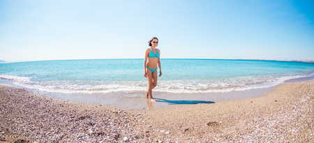Foto de A woman in a bathing suit walking along a stony shore. The girl looks at the ocean. Brunette resting on the beach of the Mediterranean Sea. Winter holidays in Turkey. The girl comes out of the water. - Imagen libre de derechos