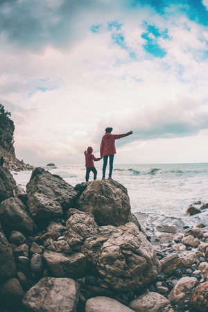 Photo pour A woman with her son are standing on a stone and looking at the sea. The boy with his mother look at the waves. The child is walking along the ocean shore. Silhouette of mom and child against the sky. - image libre de droit