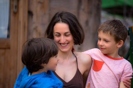 Photo pour Woman hugging sons on the terrace of a wooden house. Boys spend time with mom. Young mother walks with children. A happy family. Young brunette fooling around with a child. - image libre de droit
