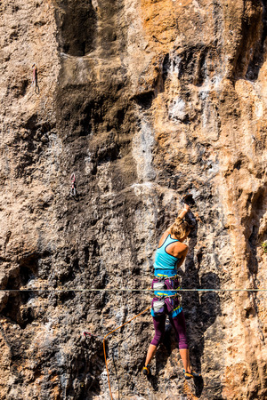 Photo pour A girl climbs a rock. The athlete trains in nature. Woman overcomes difficult climbing route. Strong climber. Extreme hobby. - image libre de droit