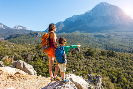 Photo for The boy and his mother are standing on the top of the mountain. A woman is traveling with child. Boy with his mother looking at the mountains. Travel with backpacks. Hike and climb with kids. - Royalty Free Image