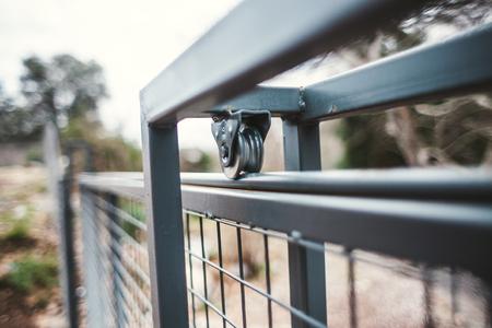 Photo pour The mechanism closes the gate. Metal fence. Wheel for opening the door. Protection against penetration. - image libre de droit