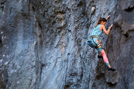 Photo pour Climber overcomes challenging climbing route. A girl climbs a rock. Woman engaged in extreme sport. Extreme hobby. - image libre de droit