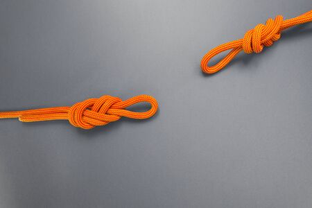 Orange climbing rope on a grey background. Safety knot. The knot the eight for safety.