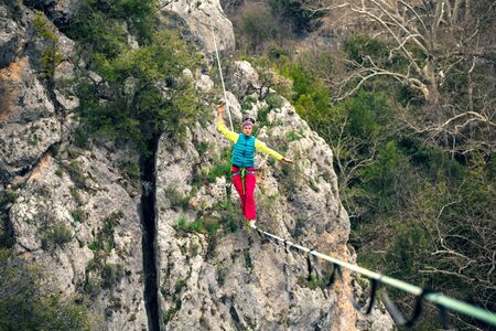 Photo for A woman is walking along a stretched sling. Highline in the mountains. Woman catches balance. Performance of a tightrope walker in nature. - Royalty Free Image
