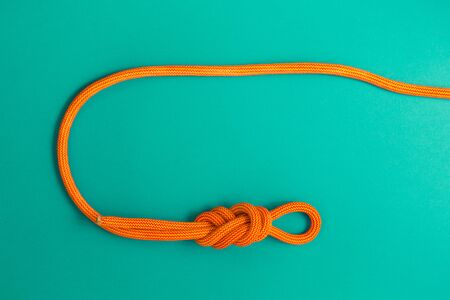 Orange climbing rope on a blue background. Safety knot. The knot the eight for safety.