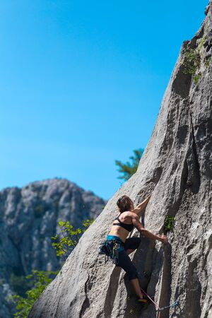 Foto de Rock climbing and mountaineering in the Paklenica National Park. A woman overcomes a challenging climbing route on natural terrain. Climber trains on the rocks of Croatia. - Imagen libre de derechos