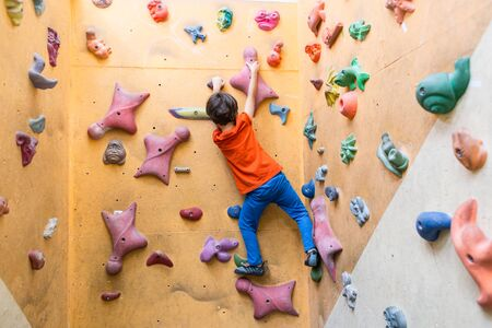 Photo pour boy is training on artificial boulders in the gym, bouldering. Extreme sports. A child climbs on a children's climbing wall. - image libre de droit