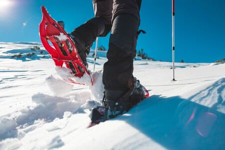 Photo for A man in snowshoes. Equipment for winter hiking in the mountains. Feet on the snow close-up. Active lifestyle. Journey in the mountains in winter. Extreme vacation in nature. - Royalty Free Image