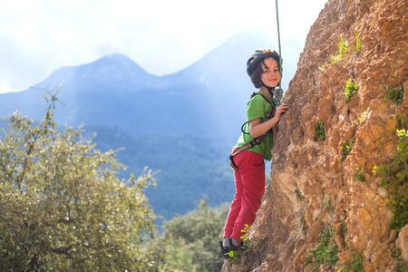 Photo for The child is climbing on a natural terrain. A boy climbs a rock on a background of mountains. Extreme hobby. Athletic kid trains to be strong. Rock climbing safety. - Royalty Free Image