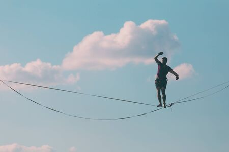 Photo pour Highliner on the background of blue sky makes a move. A man is walking along a stretched sling. Performance tightrope walker. Man balances over the abyss. A decisive step forward. - image libre de droit