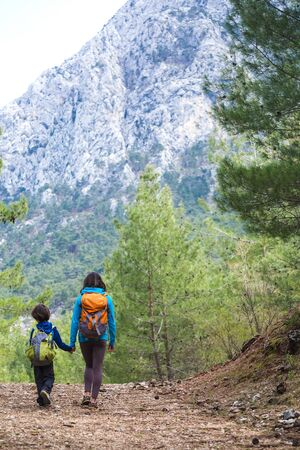 Photo for A woman with a backpack leads a child by the hand along a mountain trail, A boy travels with his mother, Hiking with children, Travel to the picturesque places of Turkey. - Royalty Free Image