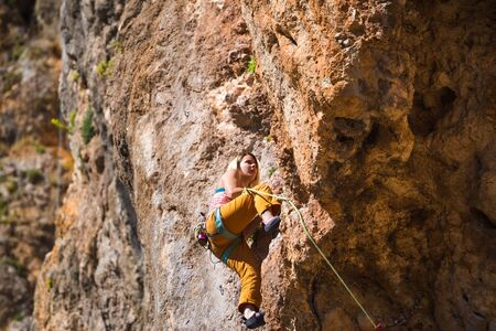 Photo pour A girl climbs a rock. The athlete trains in nature. Woman overcomes difficult climbing route. Strong climber. Extreme hobby. Rock climbing in Turkey. - image libre de droit