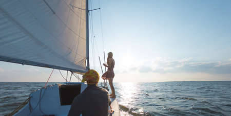 Photo for Romantic couple in love on sail boat traveling under sunlight on yacht, A man and a woman are on a sailing yacht. - Royalty Free Image