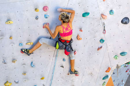 Photo for A woman climbs a climbing wall, a climber is training on artificial terrain, rock climbing in the city, a strong girl, sports in the city, safety in extreme sports. - Royalty Free Image