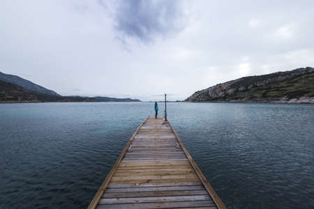 Photo pour A girl stands on the pier and looks at the sea, a woman stands in the middle of the pier, a trip to picturesque places, a girl against the background of a lake, mountains and a cloudy sky, cold season - image libre de droit