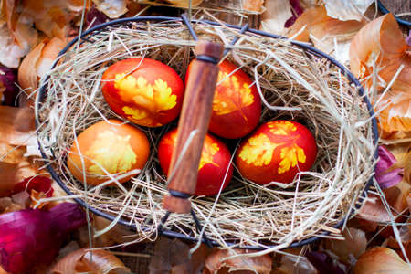 Photo pour Painted Easter eggs with a pattern of leaves in a metal basket, top view - image libre de droit