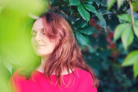 Photo pour A woman in a red dress in nature, copy space - image libre de droit