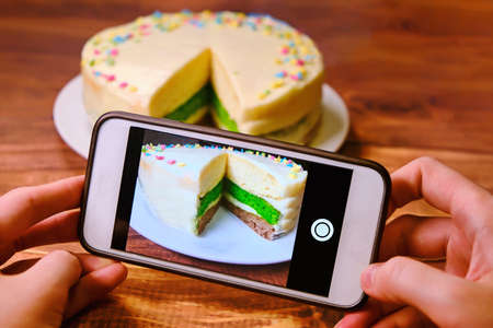 Photo for Women's hands with the phone taking pictures of the cake. Blogger shoots food . Create a photo for posting on the Internet. White phone and a tri-color cake on a wooden table. - Royalty Free Image