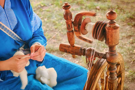 Photo pour Distaff creates a thread from a spindle. Manual spinning wheel outdoors, lifestyle. - image libre de droit