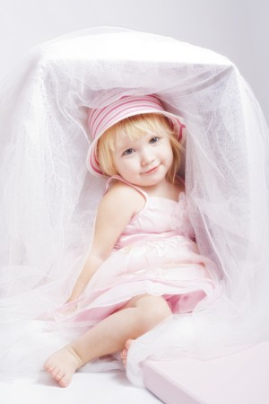 Pretty baby-girl in beautiful pink dress and bonnet sit in big box like a doll