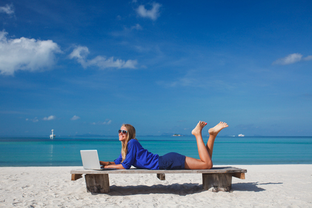 Photo pour Beautiful young woman working with laptop on the tropical beach - image libre de droit