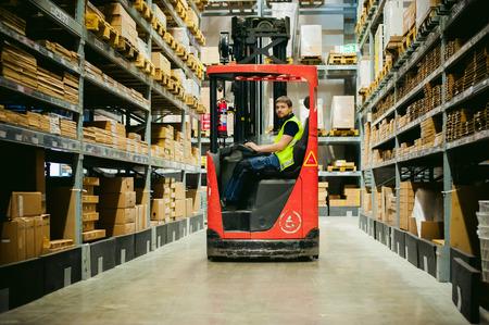 Foto de young man in working clothes, driver Reachtruck busy working on the logistics warehouse store - Imagen libre de derechos