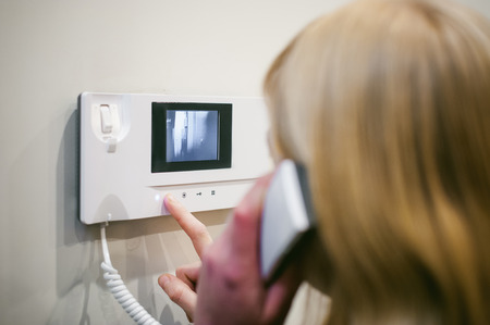 Photo pour blonde woman answers the intercom call while holding the phone to your ear - image libre de droit
