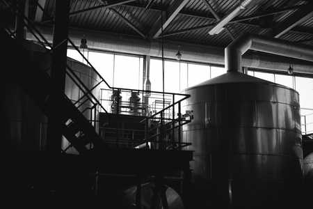 Beer manufacture line. Equipment for staged production bottling of Finished food products. Metal structures, pipes and tanks at enterprise factory. Special equipment inside within industrial premises